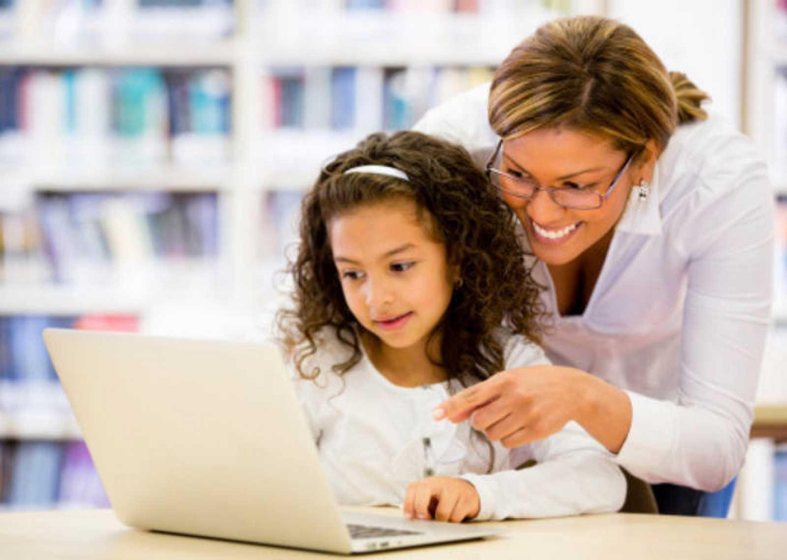 Una niña usa el ordenador portátil junto a su madre