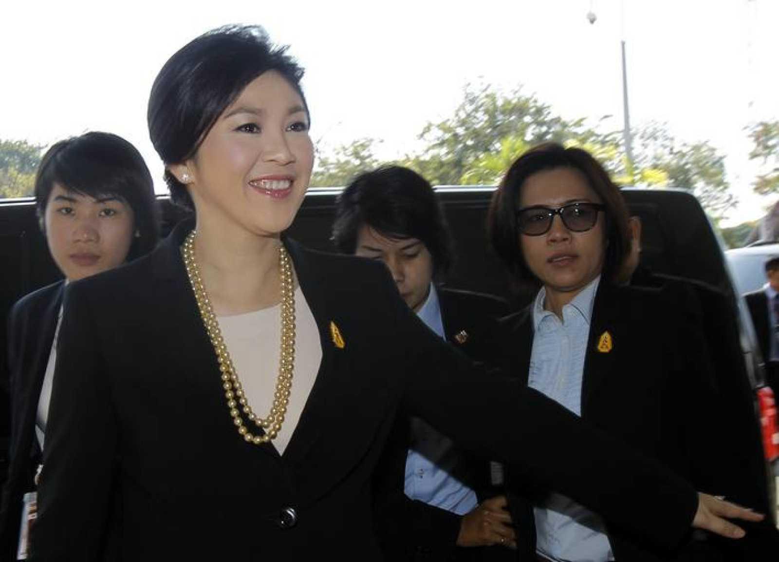 La primera ministro Yingluck Shinawatra sonríe en su llegada al Parlamento para enfrentarse a la moción de censura que ha superado