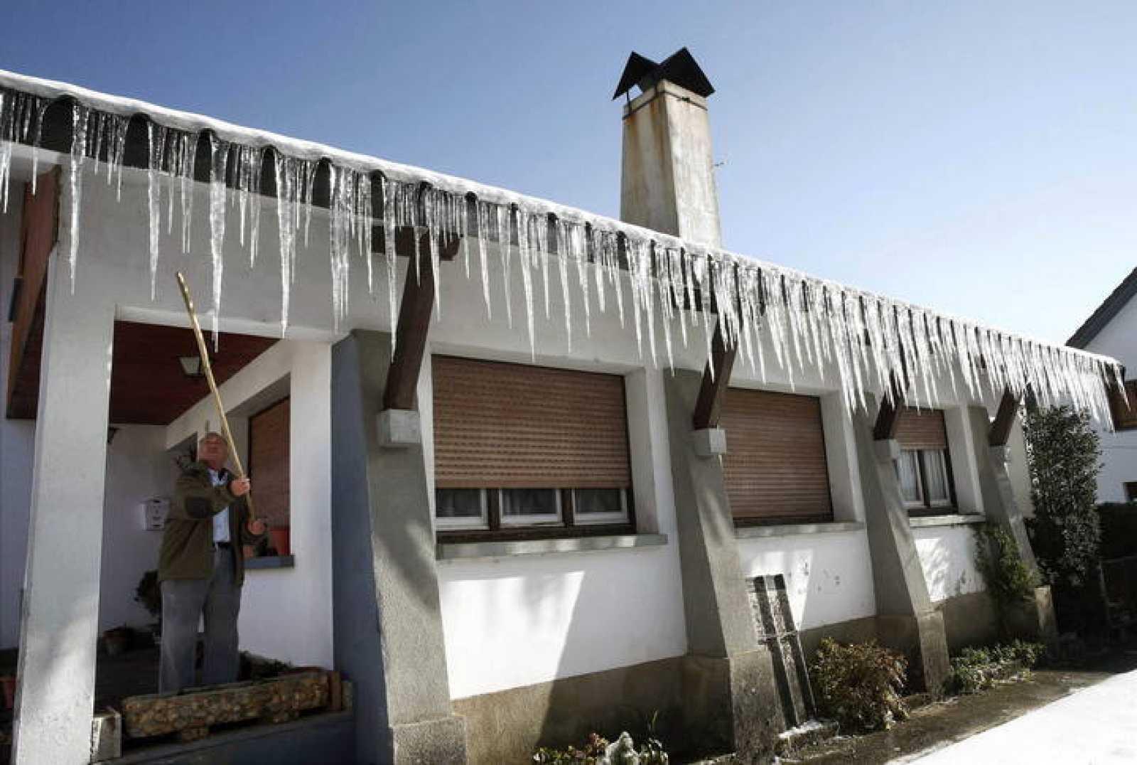 Un hombre observa los carámbanos de hielo sobre el tejado de su vivienda en Navarra