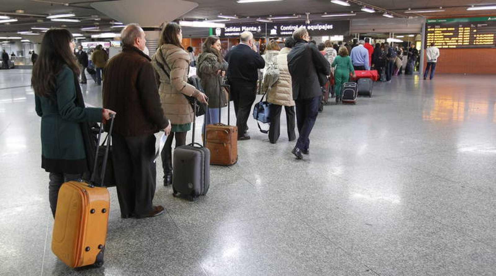 Varios viajeros hacen cola ante el control de equipajes en la estación de tren de Atocha, en Madrid