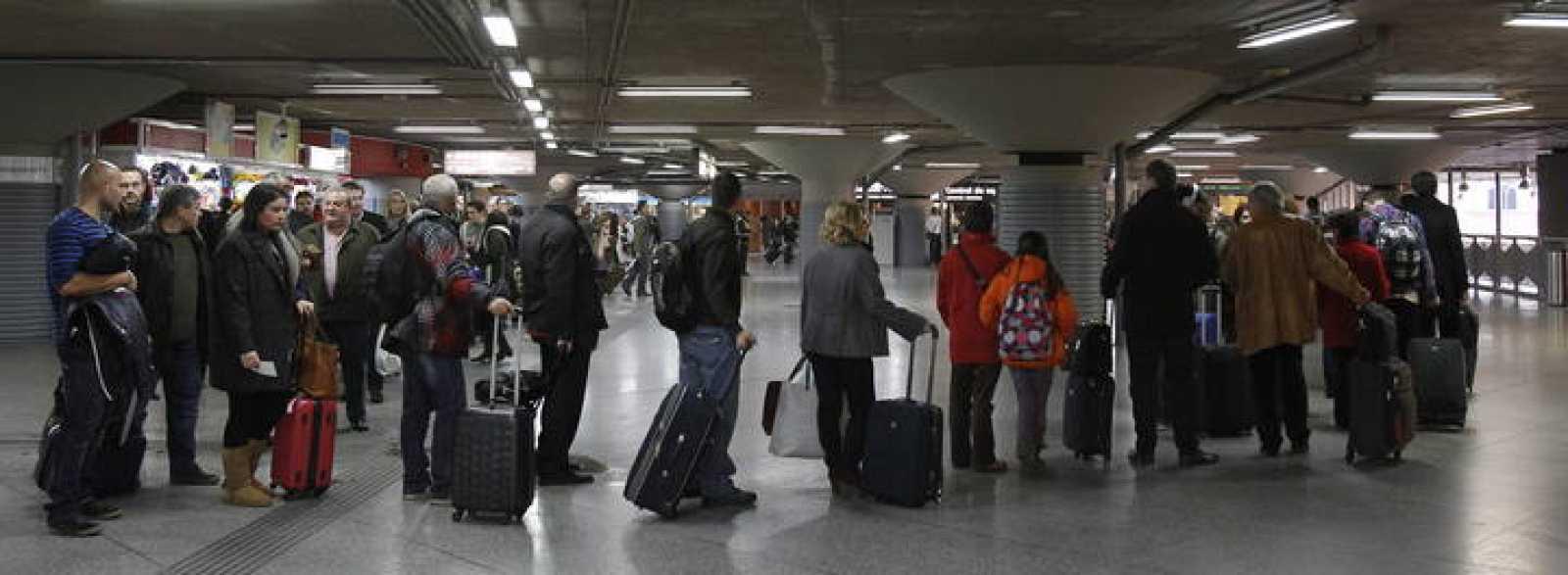 Un grupo de viajeros hacen cola en la estación de Atocha, en Madrid