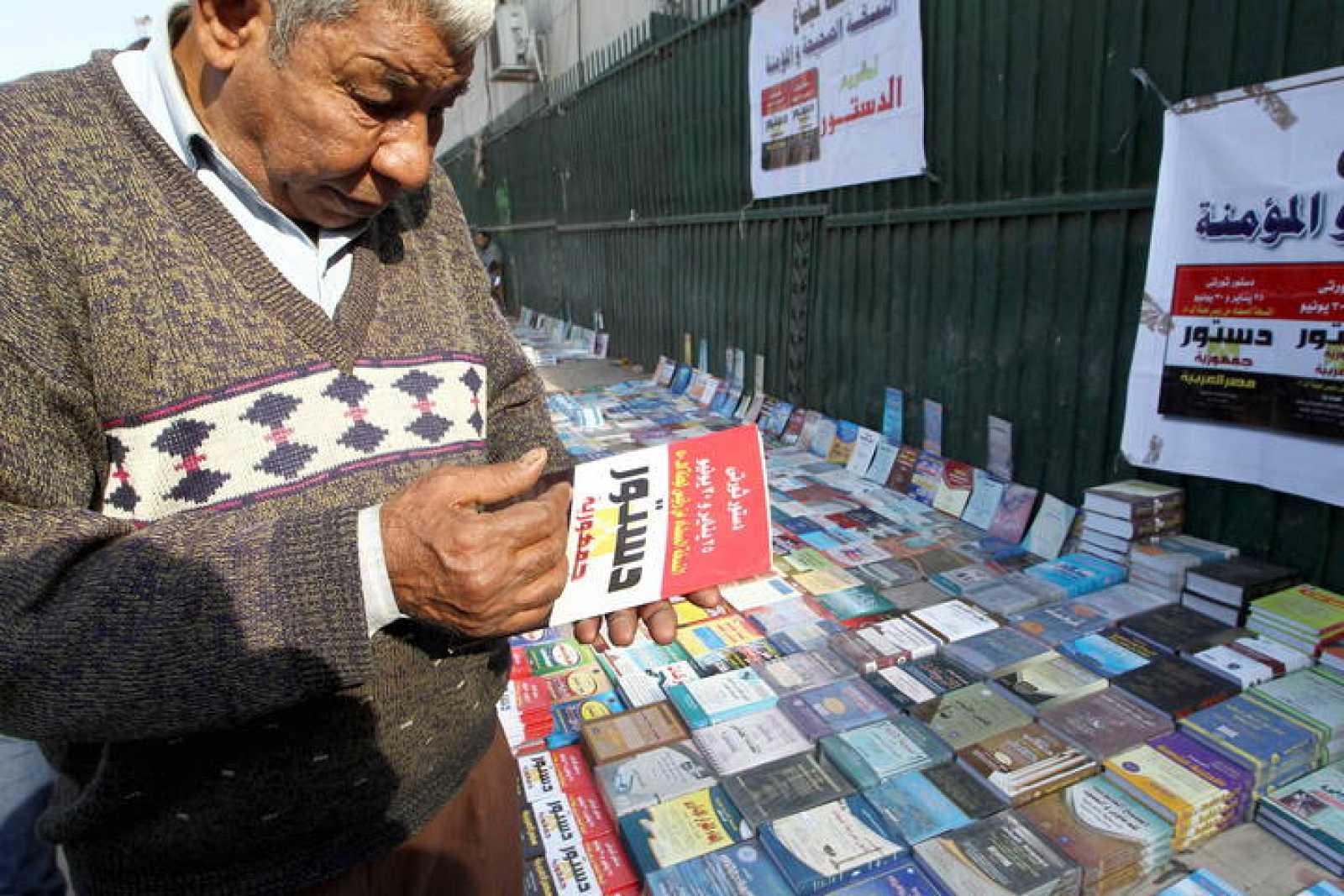 Un egpcio lee un ejemplar de la Constitución que se vota esta semana