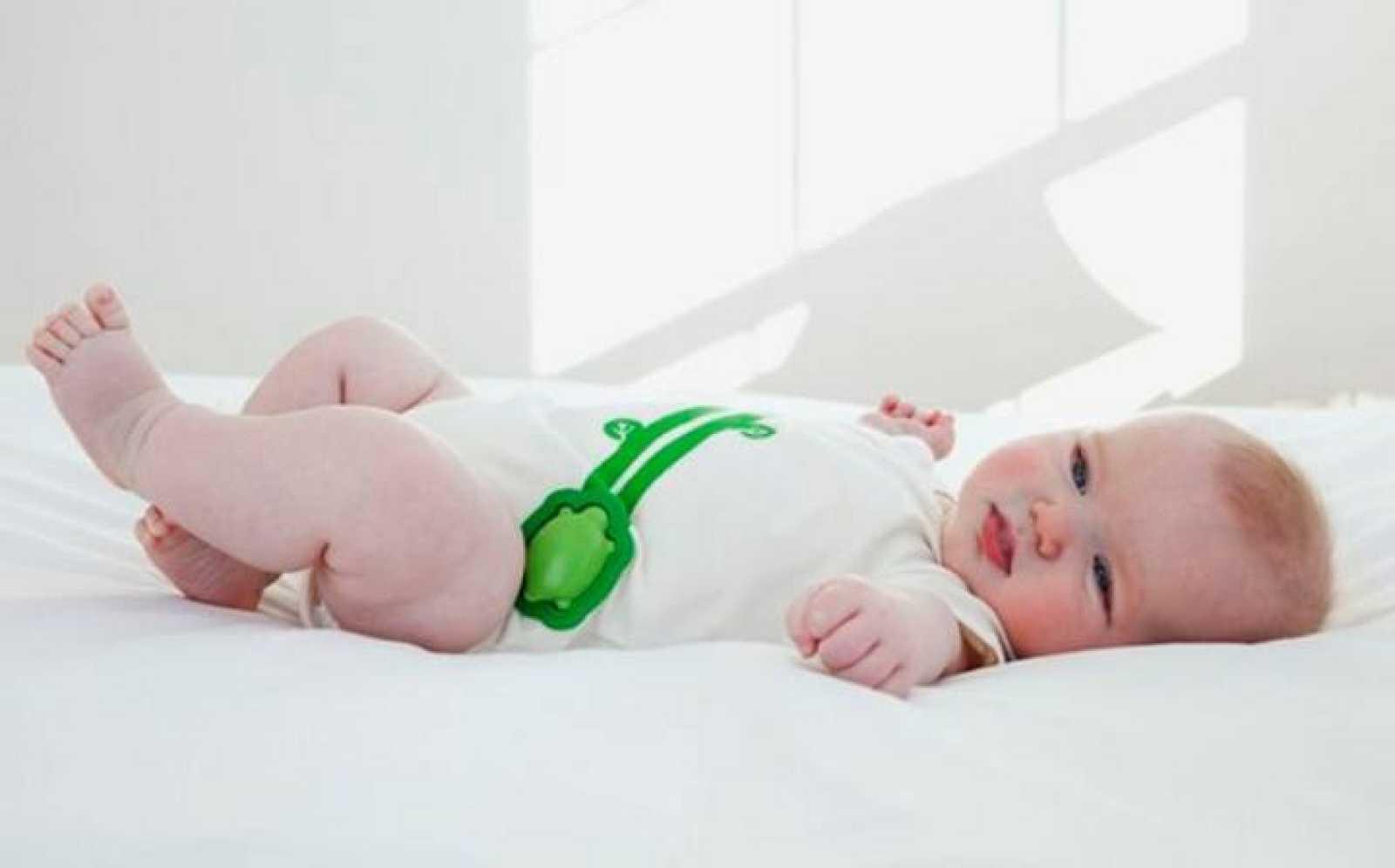 Bebé con el dispositivo que le monitoriza, envuelto en una tortuga.