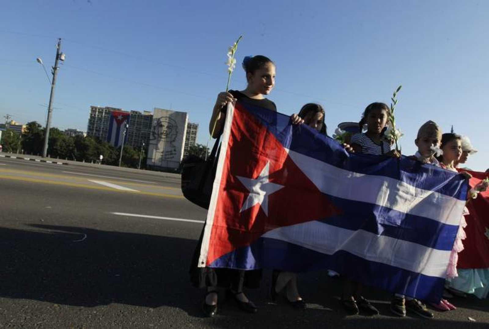 Estudiantes cubanos sostienen una bandera nacional en La Habana