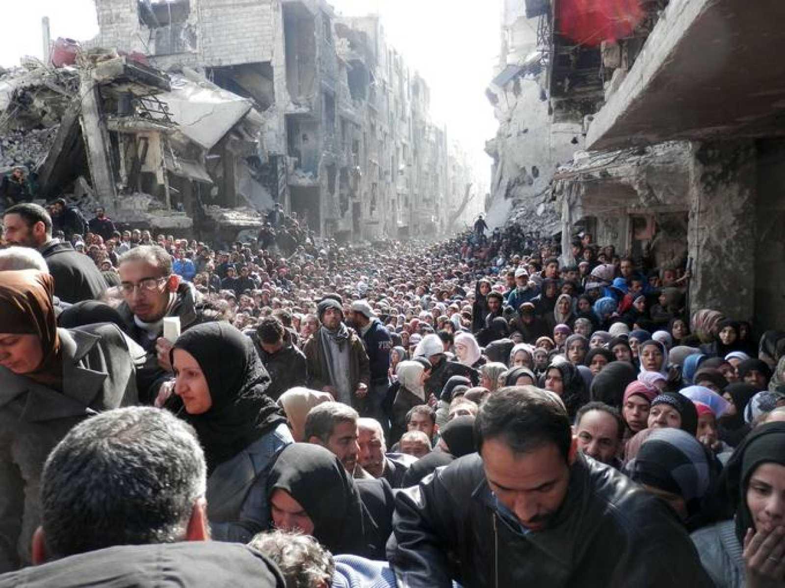 Refugiados palestinos del campo de Yarmuk, en Siria, esperan un reparto de ayuda humanitaria de la UNRWA