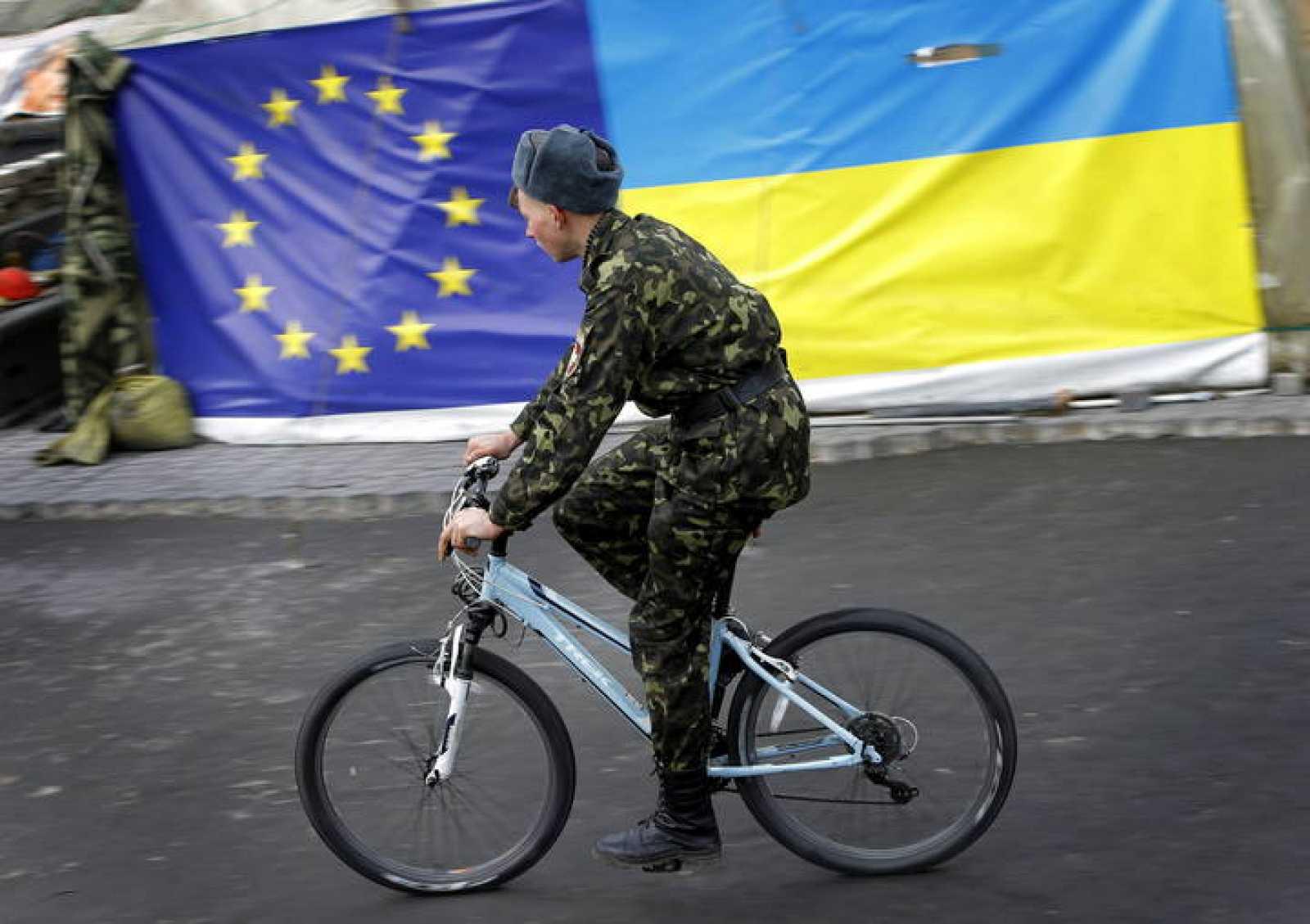"""Un miembro de las autodenominadas """"defensas"""" de maidán pasa junto a banderas de la UE y Ucrania"""