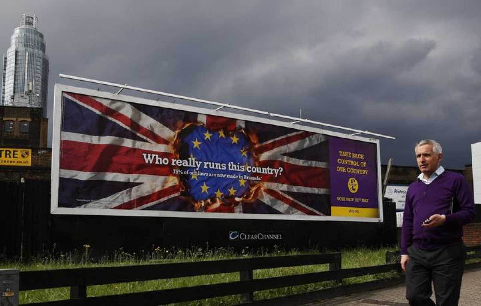 A pedestrian passes above a United Kingdom Independence Party European elections campaign poster in Vauxhall, central London