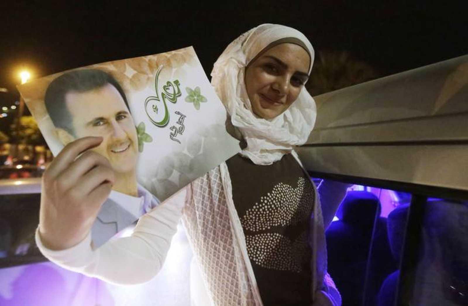 Una mujer sostiene un cuadro de Al Assad que muestra orgullosa al celebrar la victoria del político.