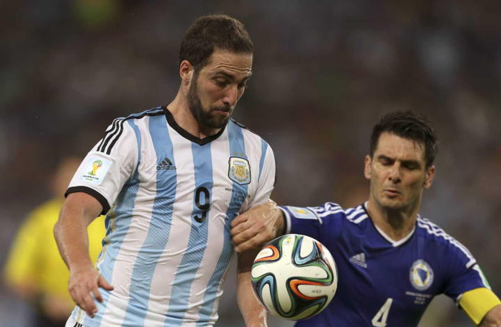 El delantero argentino Gonzalo Higuaín y el defensa bosnio Emir Spahic luchan por el balón durante el partido Argentina-Bosnia.