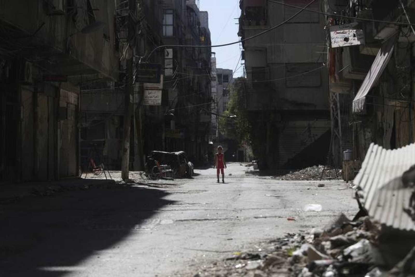 Una niña en una calle destruida en un suburbio de Damasco