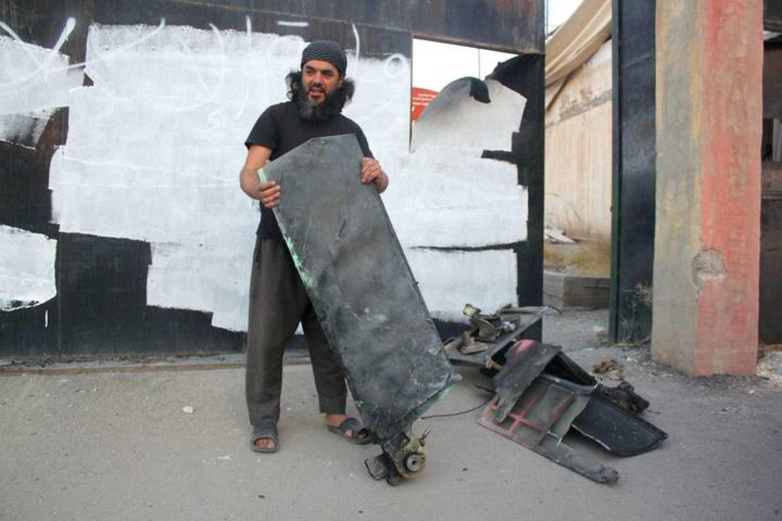 Un miliciano del Estado Islámico sostiene una pieza que, asegura, pertenece a un drone estadounidense estrellado en una torre de comunicación en Raqqa, Siria.