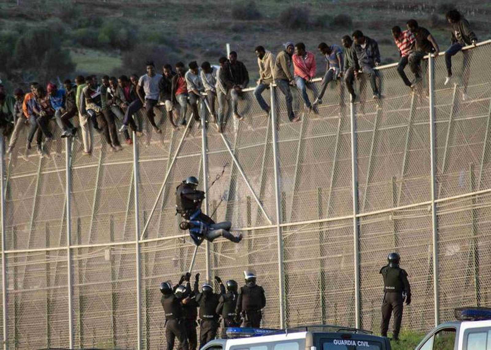 Un agente de la Guardia Civil detiene en la valla de Melilla a un inmigrante subsahariano
