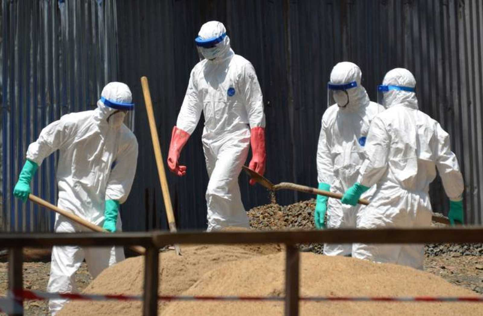 Trabajadores sanitarios recogen arena para absorber los fluidos de pacientes infectados con ébola en Sierra Leona.