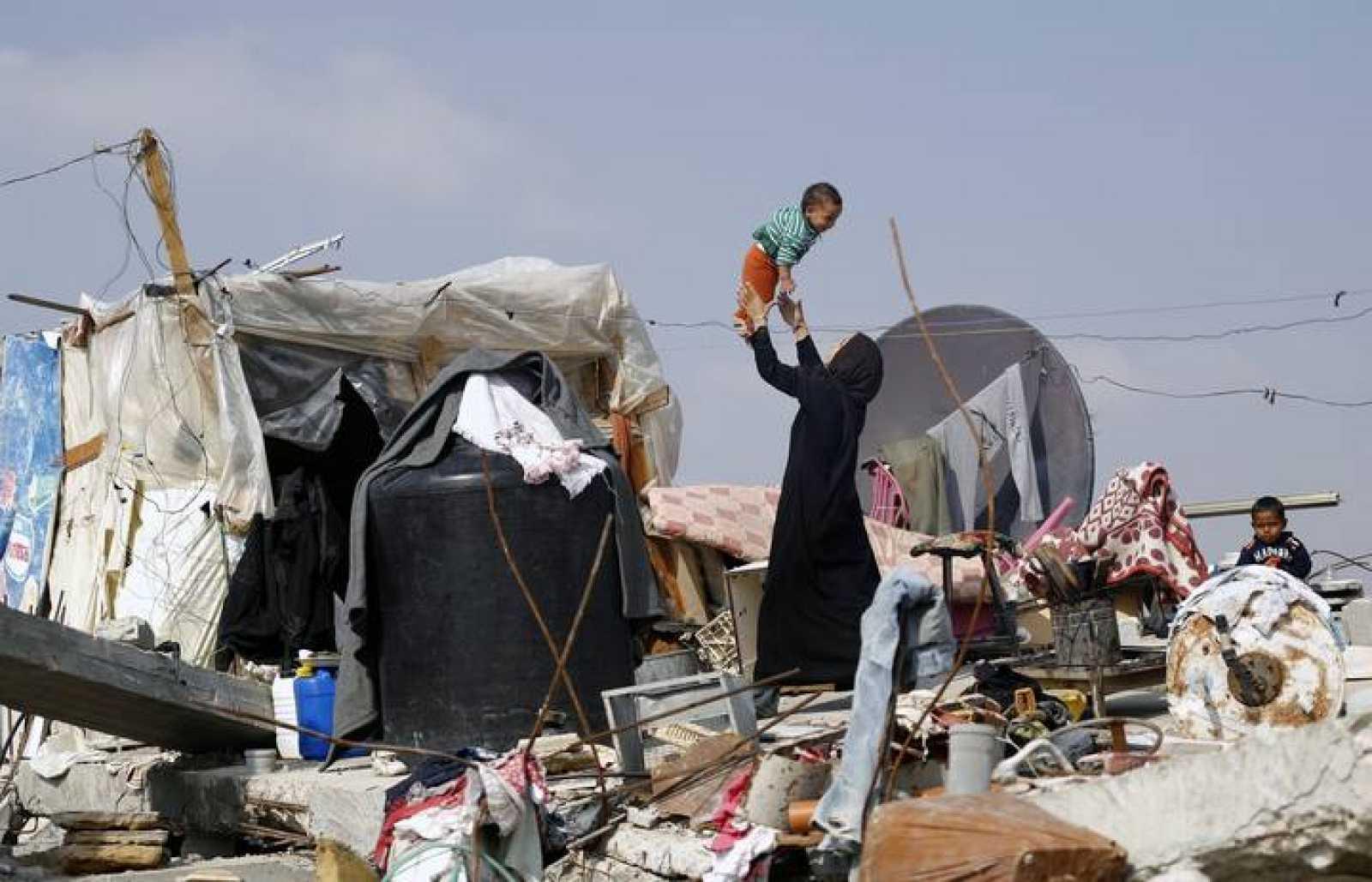 Una mujer palestina con su hijo, en Jan Yunis, entre los escombros de su casa destruida en los bombardeos israeiíes sobre Gaza
