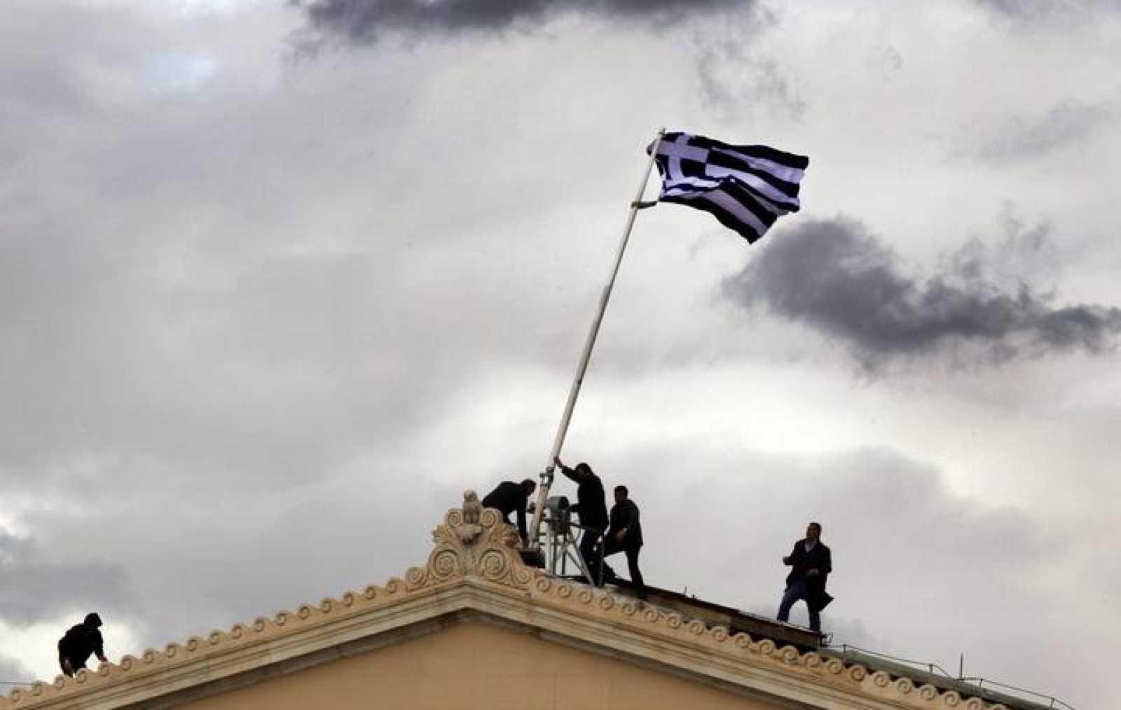 Unos operarios reemplazan la bandera de Grecia que ondea en el Parlamento griego