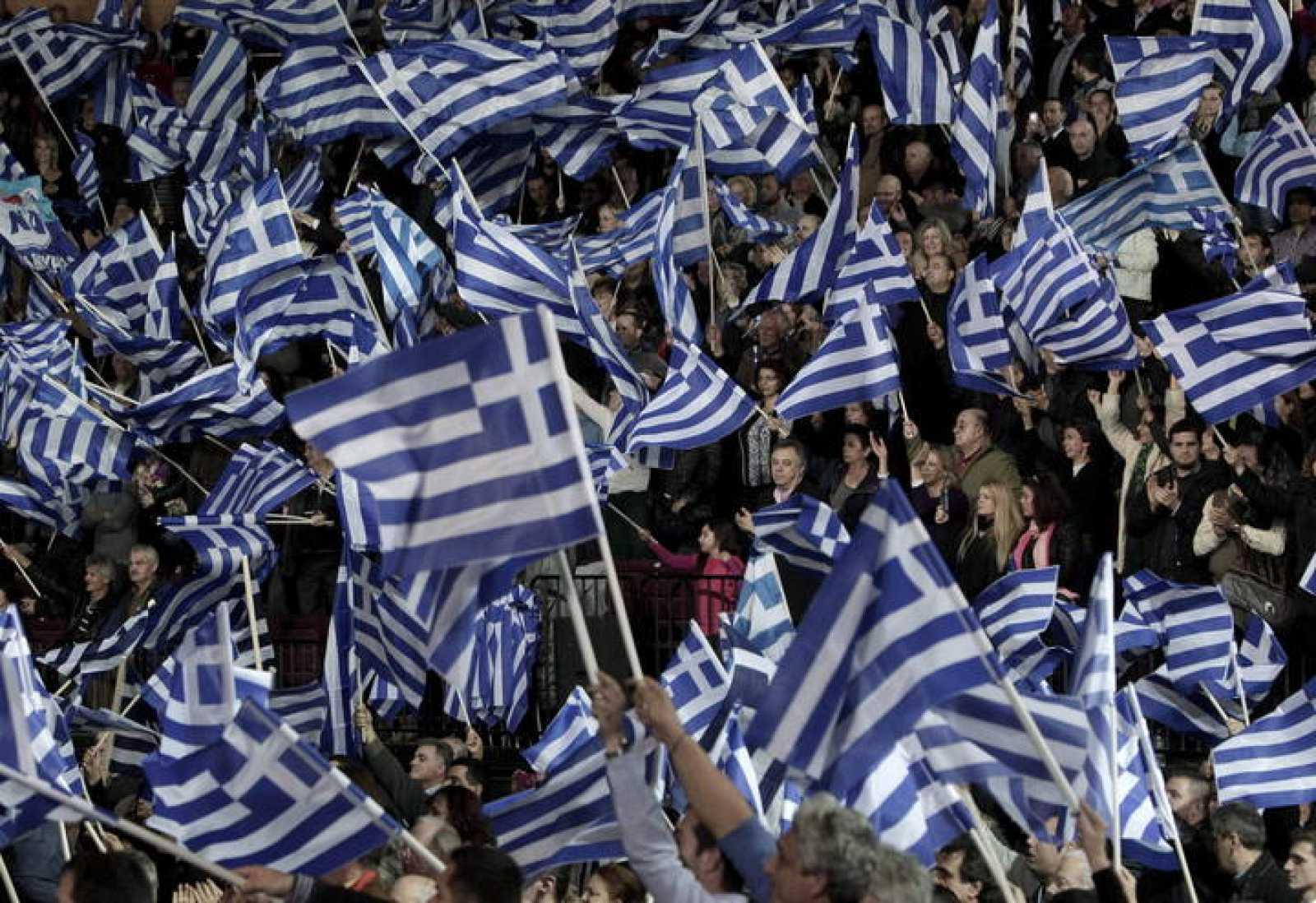 Seguidores de Nueva Democracia portan banderas en un mitin en Grecia