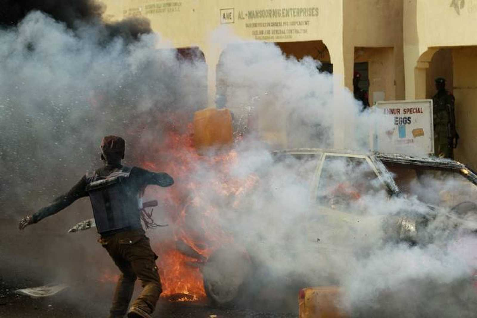 Un hombre intenta apagar las llamas del coche bomba en el estadio de Gombe, Nigeria.