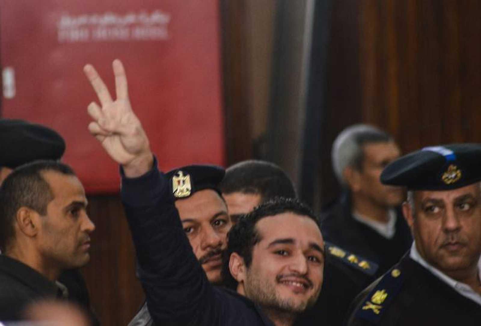 El activista Ahmed Douma hace la señal de la victoria durante el juicio en el que ha sido condenado a cadena perpetua.