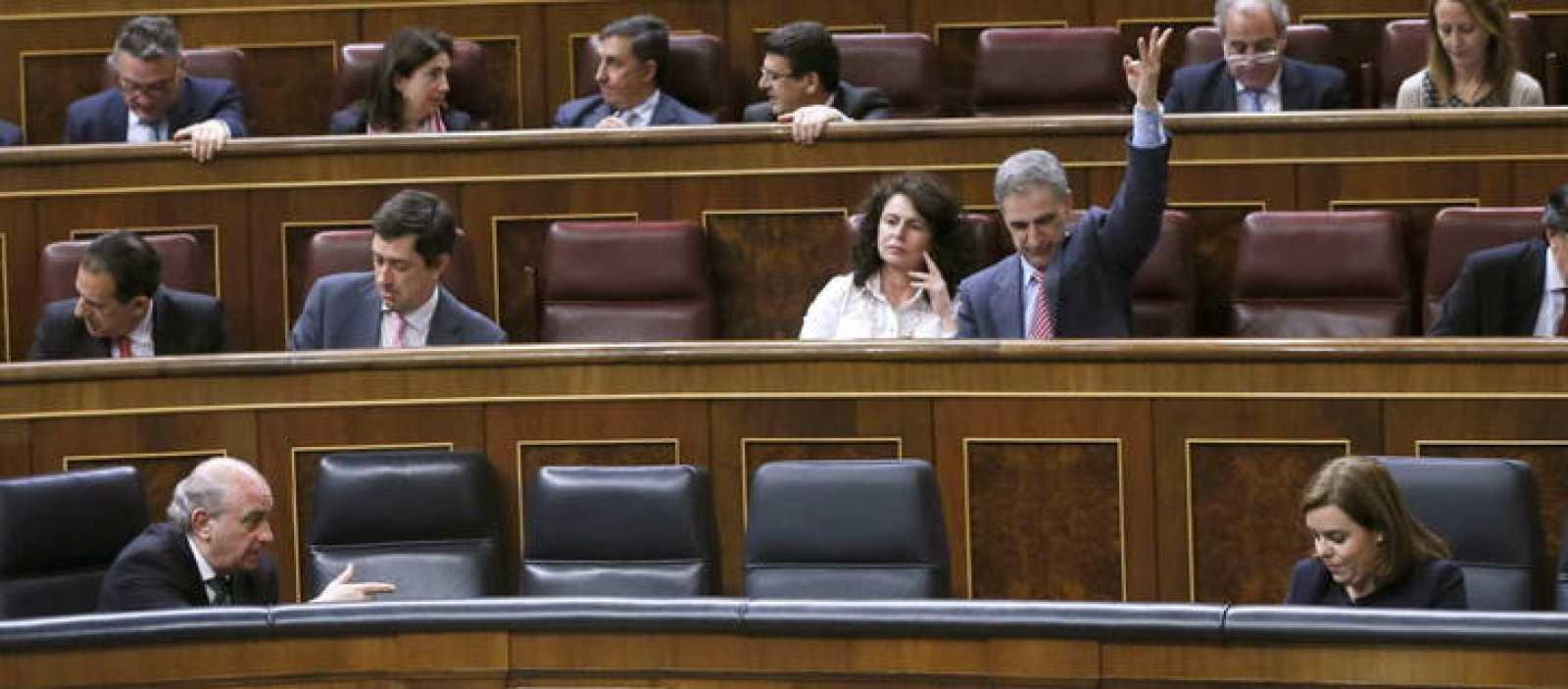 La vicepresidenta del Gobierno, Soraya Sáenz de Santamaría, conversa con el ministro del Interior, Jorge Fernández Díaz, durante el pleno del Congreso