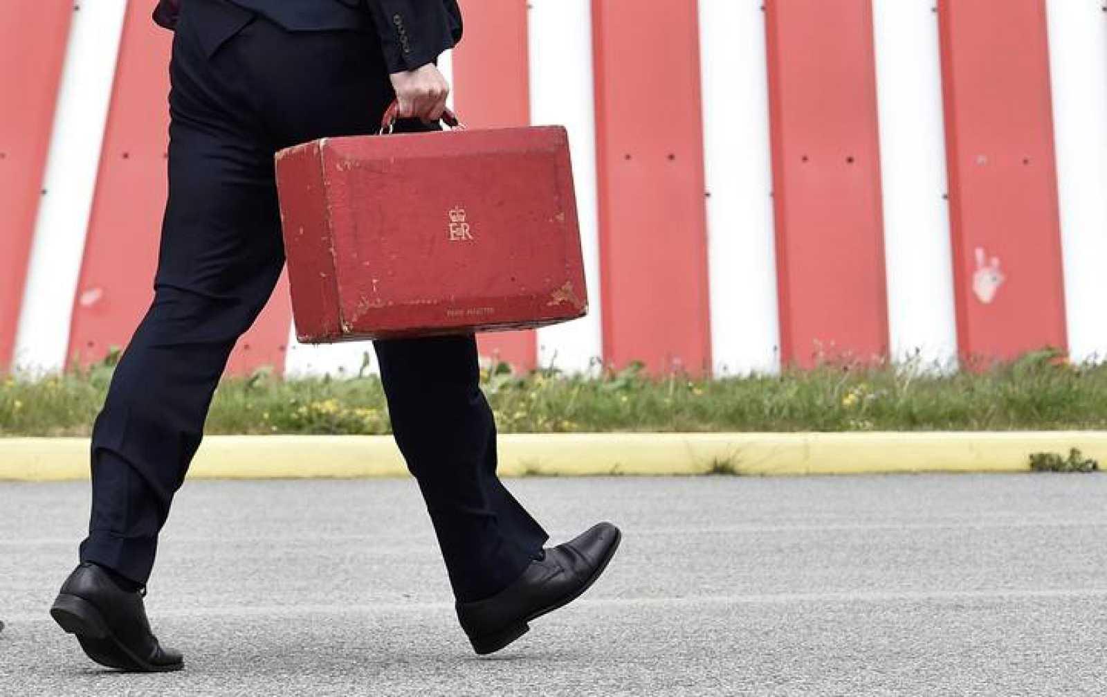 El primer ministro británico, David Cameron, camina con el maletín ministerial en el aeropuerto de Newquay, al suroeste de Inglaterra.