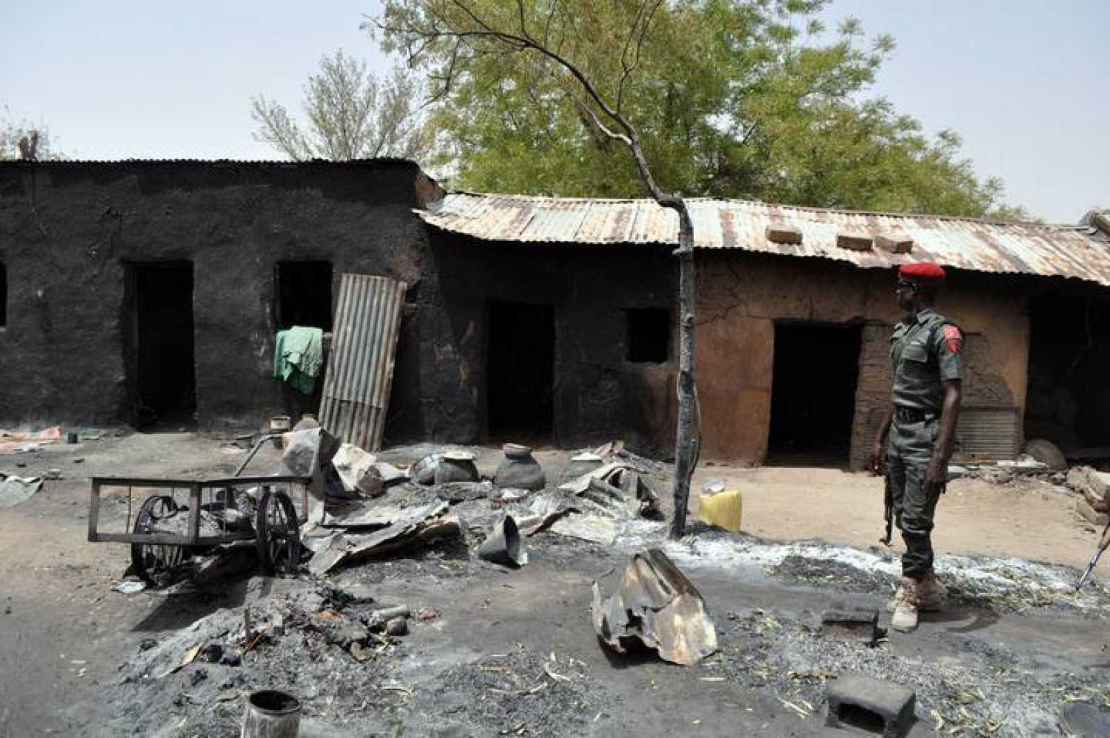 Un policía observa una casa en Gubio, estado de Borno, Nigeria, tras un ataque de Boko Haram