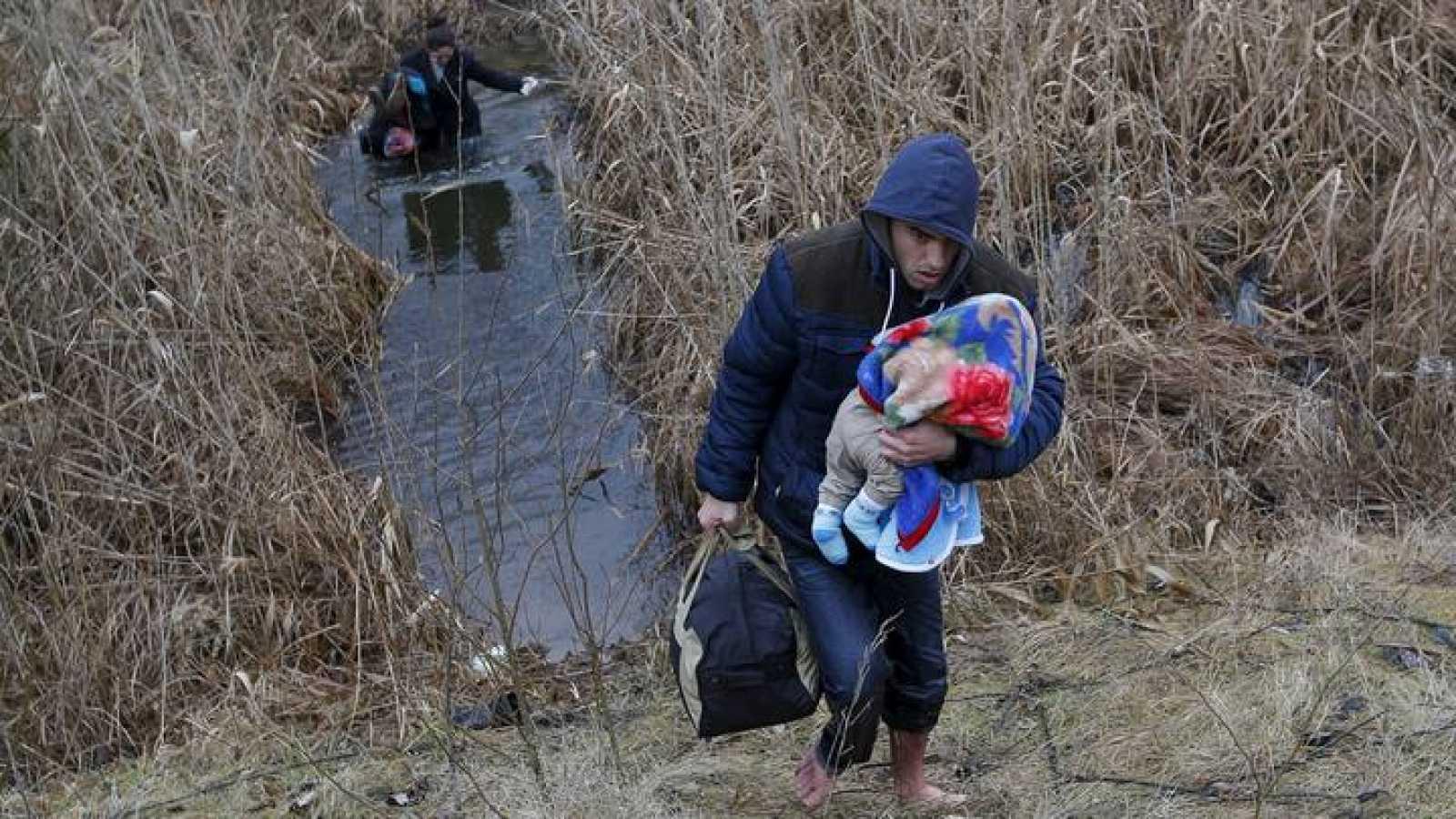 Una familia kosovar cruza clandestinamente a través de un cauce de agua la frontera entre Serbia y Hungría cerca de la localidad de Asotthalom el 6 de febrero de 2015.