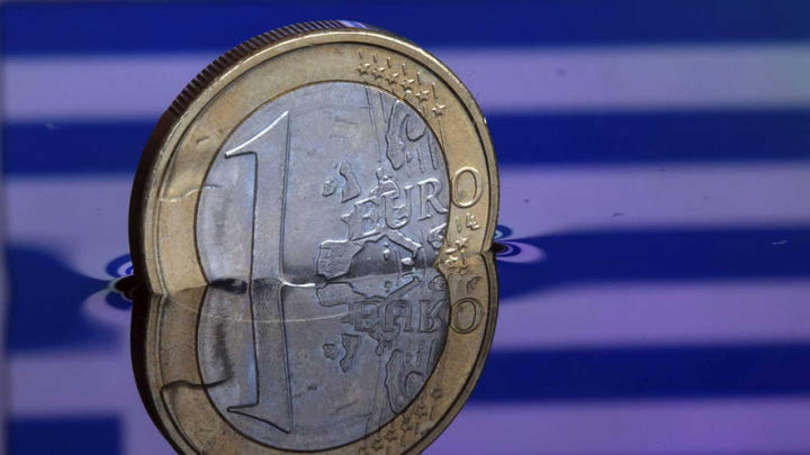 Una moneda de euro con la bandera de Grecia de fondo