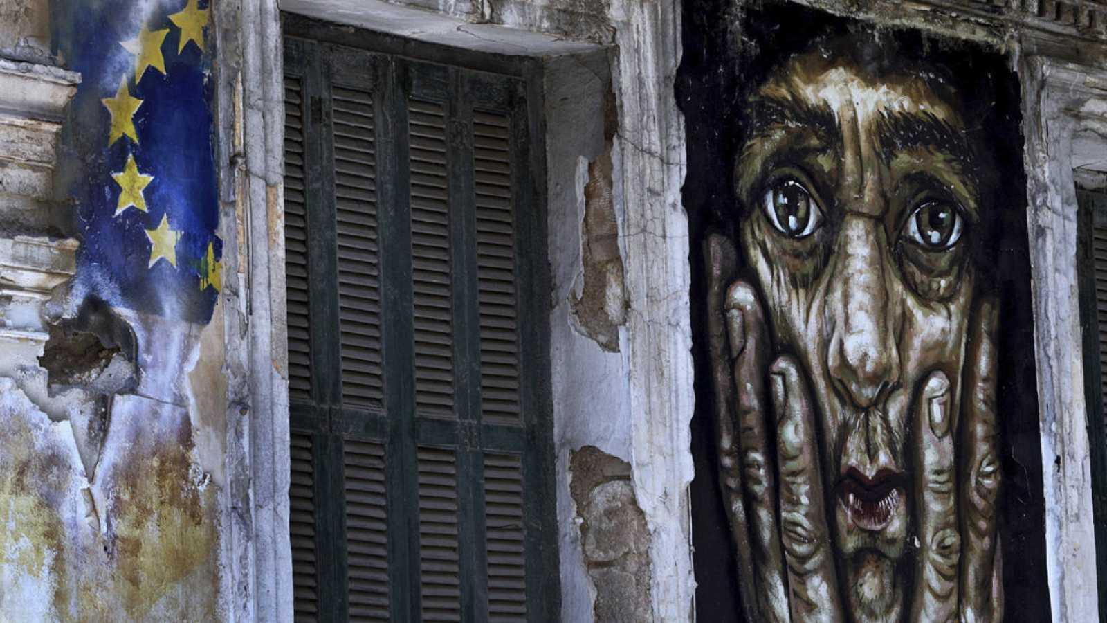 Pintada en un edificio de la bandera de la Unión Europea junto a un retrato en una pared de Atenas