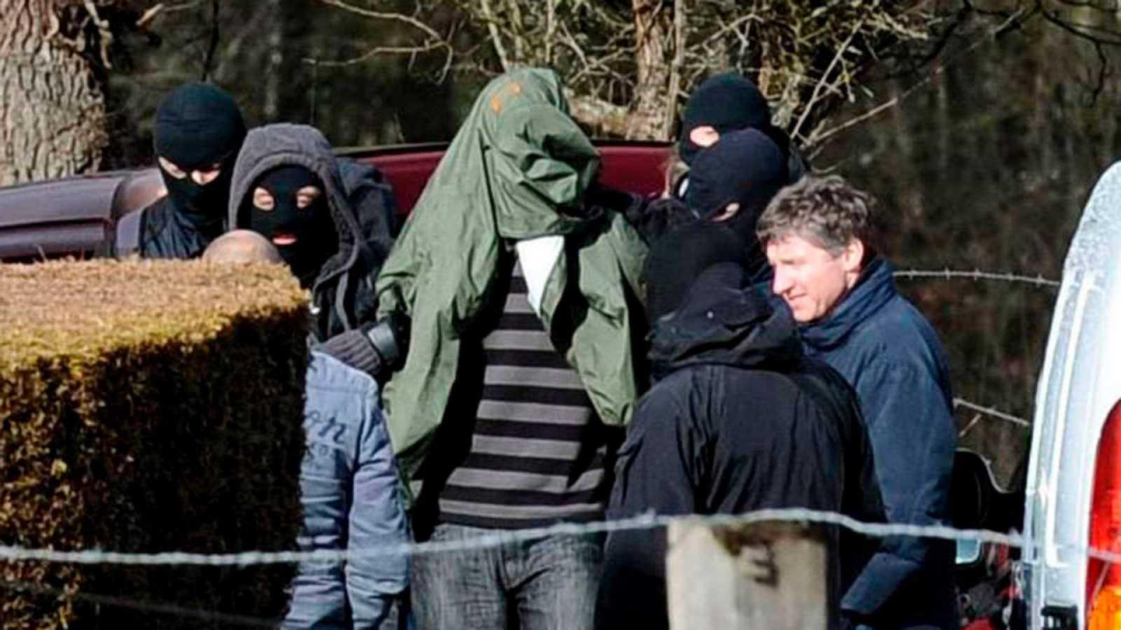 Varios agentes de la policía junto a Ibon Gogeaskoetxea, detenido en una casa rural de la localidad de Cahan, en la región de Baja Normandía (noroeste de Francia) en febrero de 2010.