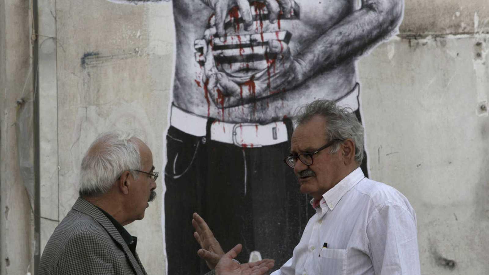 Dos hombres conversan en Atenas, delante de un graffiti que muestra un hombre que sujeta un símbolo del euro ensangrentado