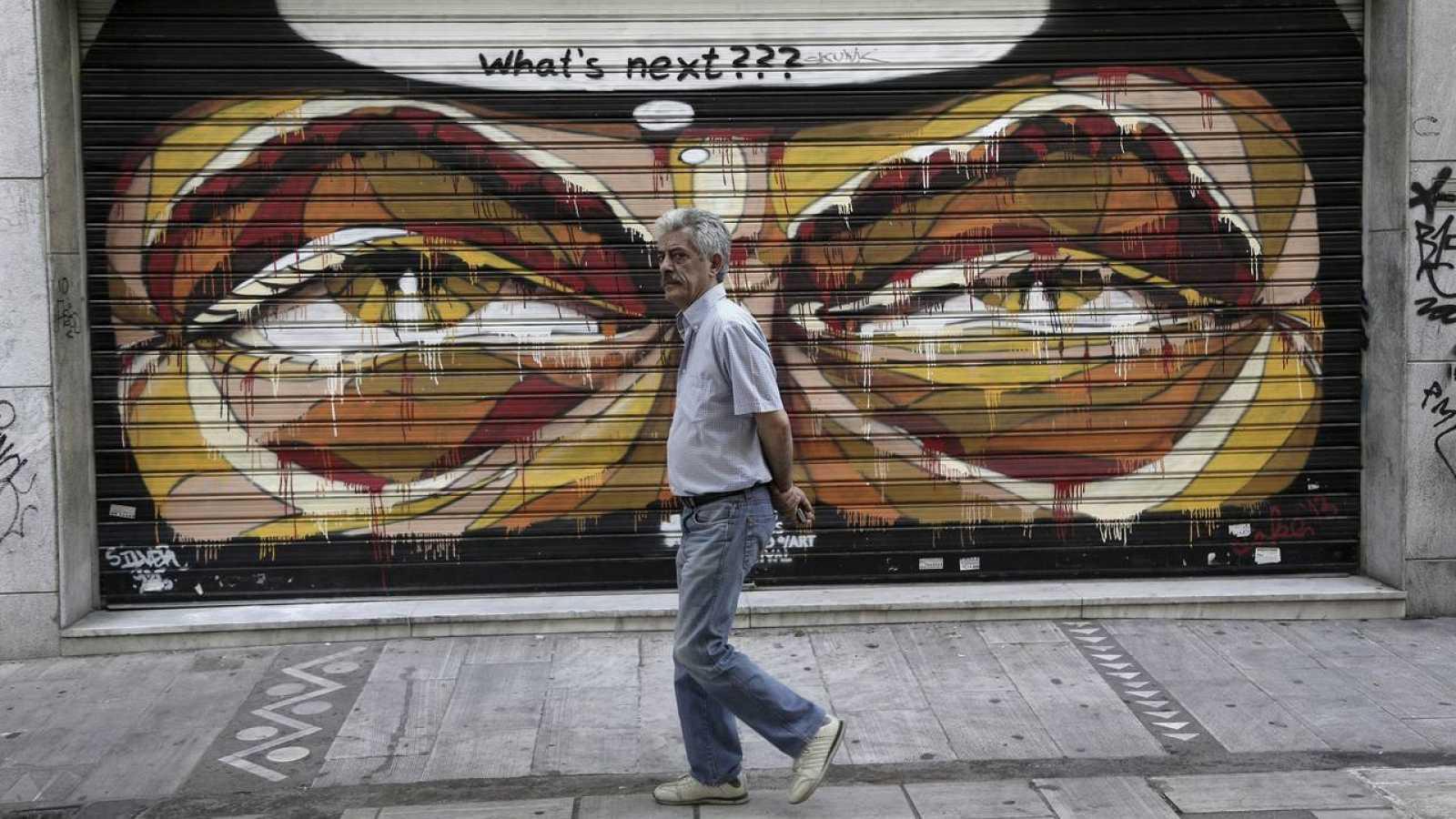 Un hombre pasa delante de un grafiti de un comercio en el centro de Atenas