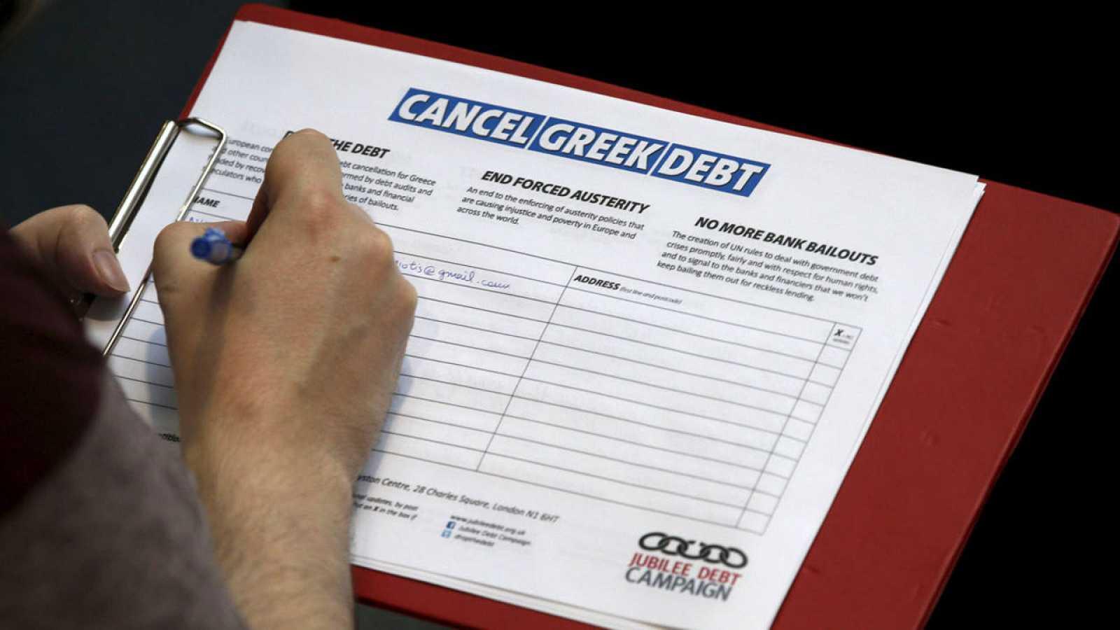 Un hombre firma la petición para cancelar la deuda de Grecia en una manifestación de apoyo a Grecia en Londres