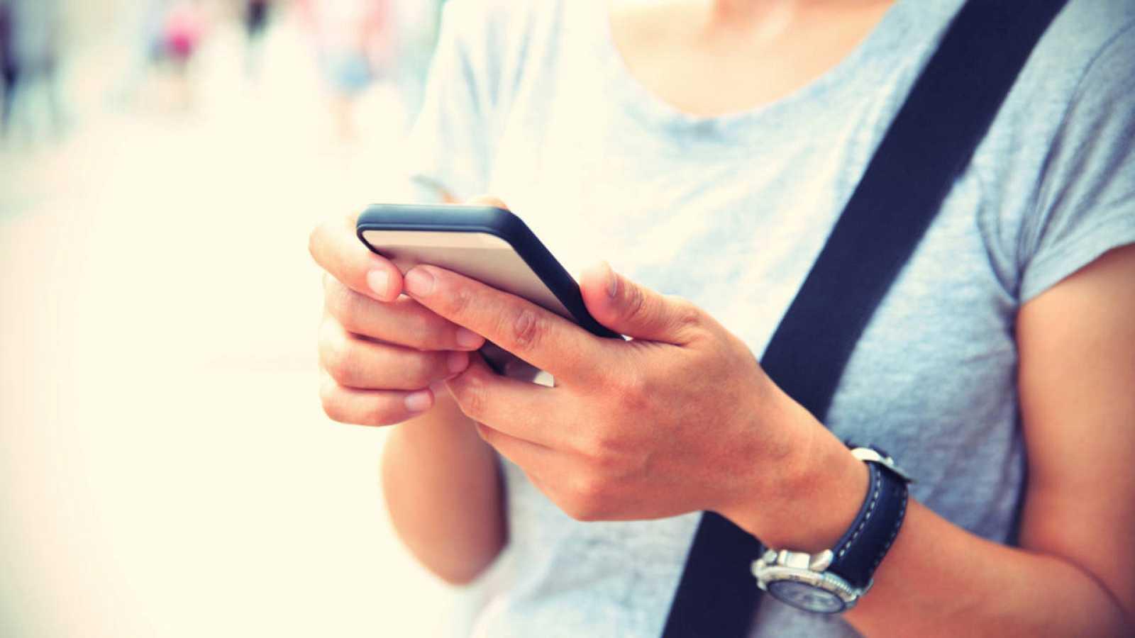 Una mujer usa su teléfono móvil
