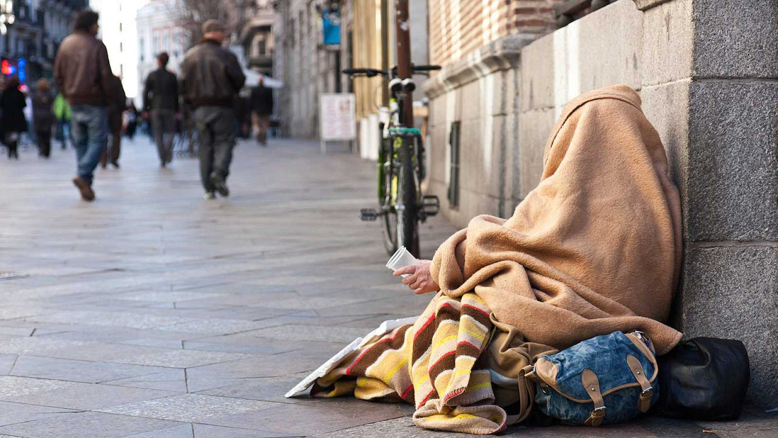 Una persona pide en una calle de Madrid.
