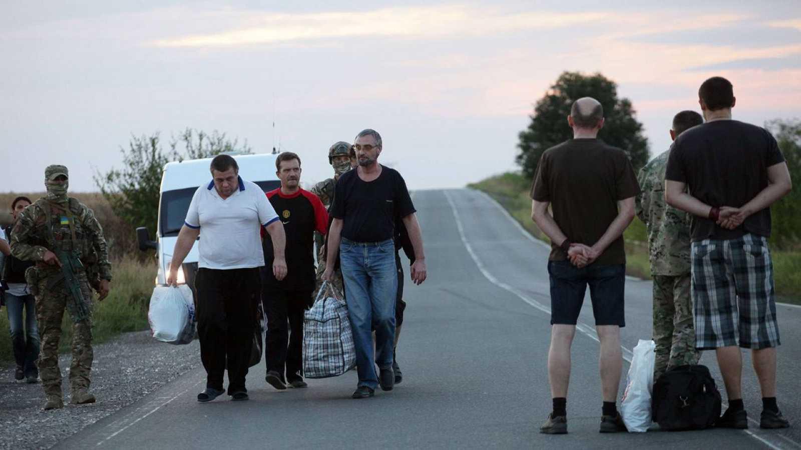 Dos rebeldes prorrusos (izquierda) son canjeados por cuatro presos del bando de Kiev en las cercanías de Donetsk este martes.
