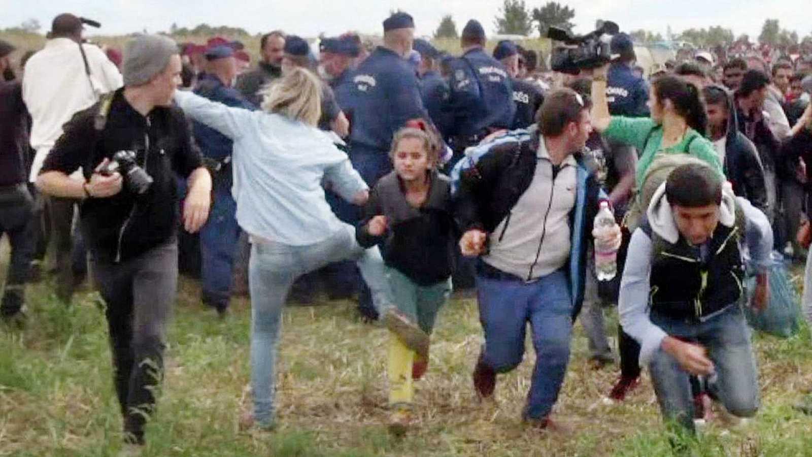 Imagen tomada de un vídeo en el que se ve a la camarógrafa húngara, Petra László (en el centro, con camisa vaquera), dando una patada a una niña que huye, en Roszke, Hungría AFP PHOTO / INDEX.HU