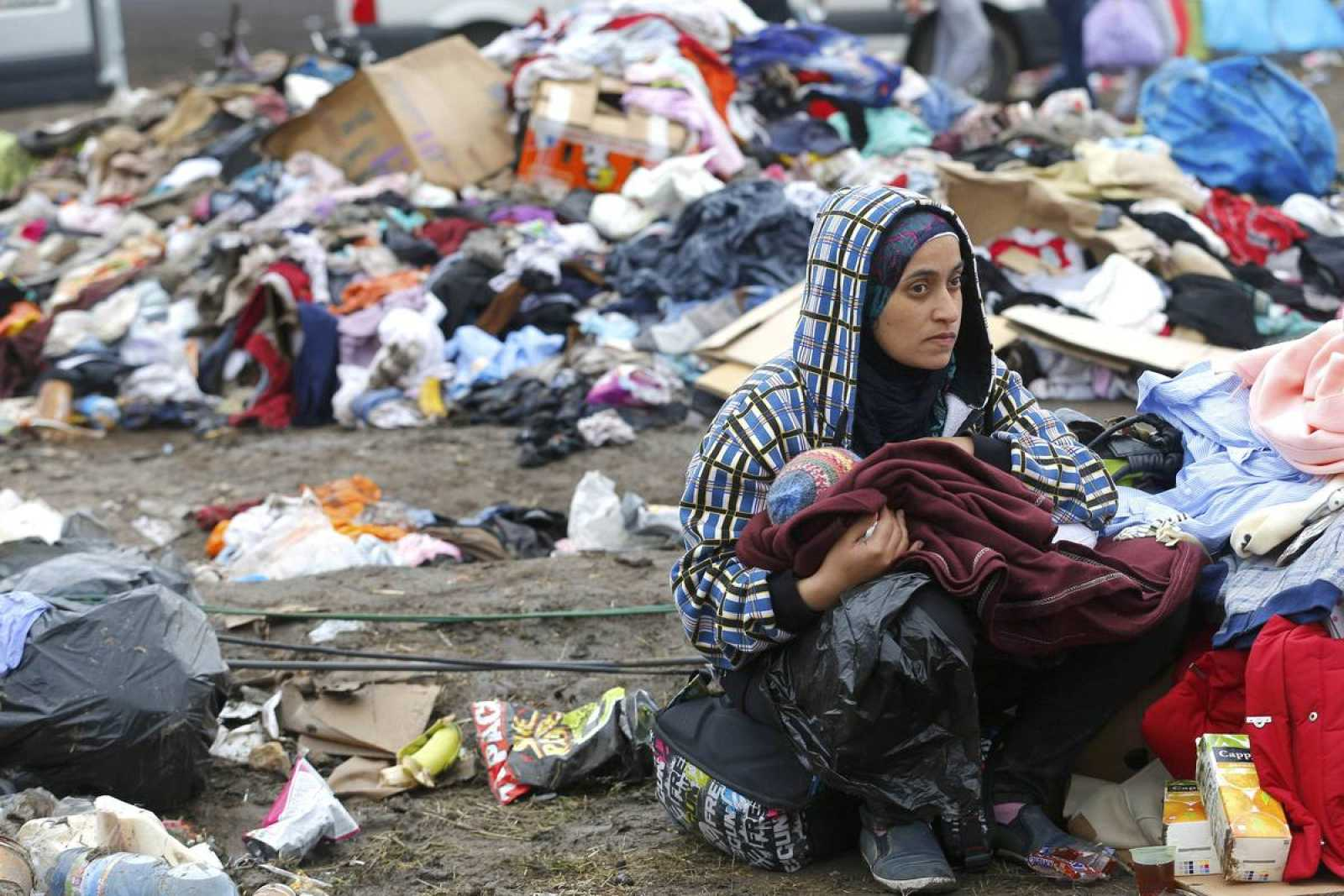 Una migrante da el pecho a su hijo rodeada de una pila de basura en un campo de refugiados en Roszke, Hungría