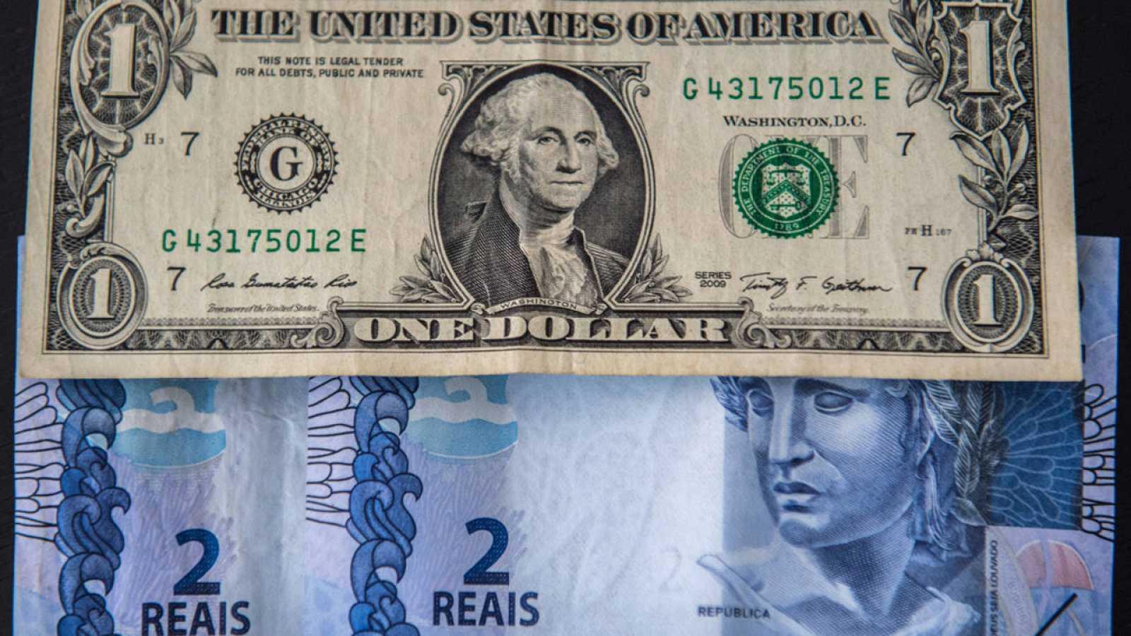 Un billete de un dólar junto a dos billetes de dos reales