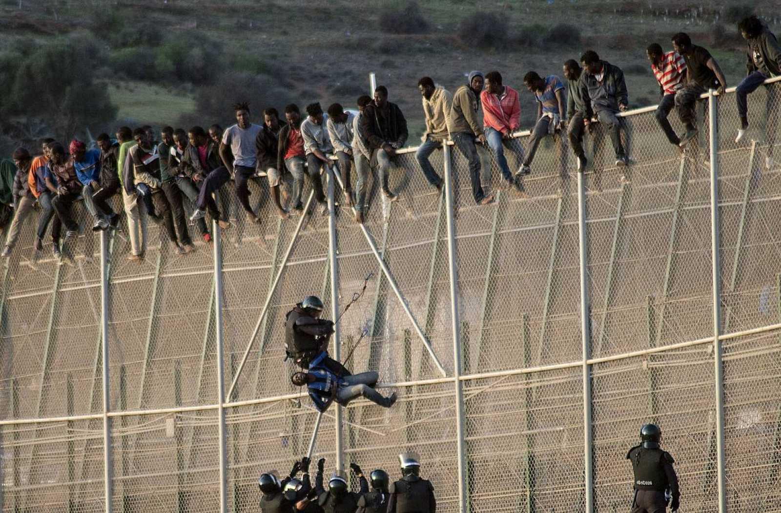 La Guardia Civil impide a un grupo de migrantes cruzar la valla de Melilla en una imagen de archivo.