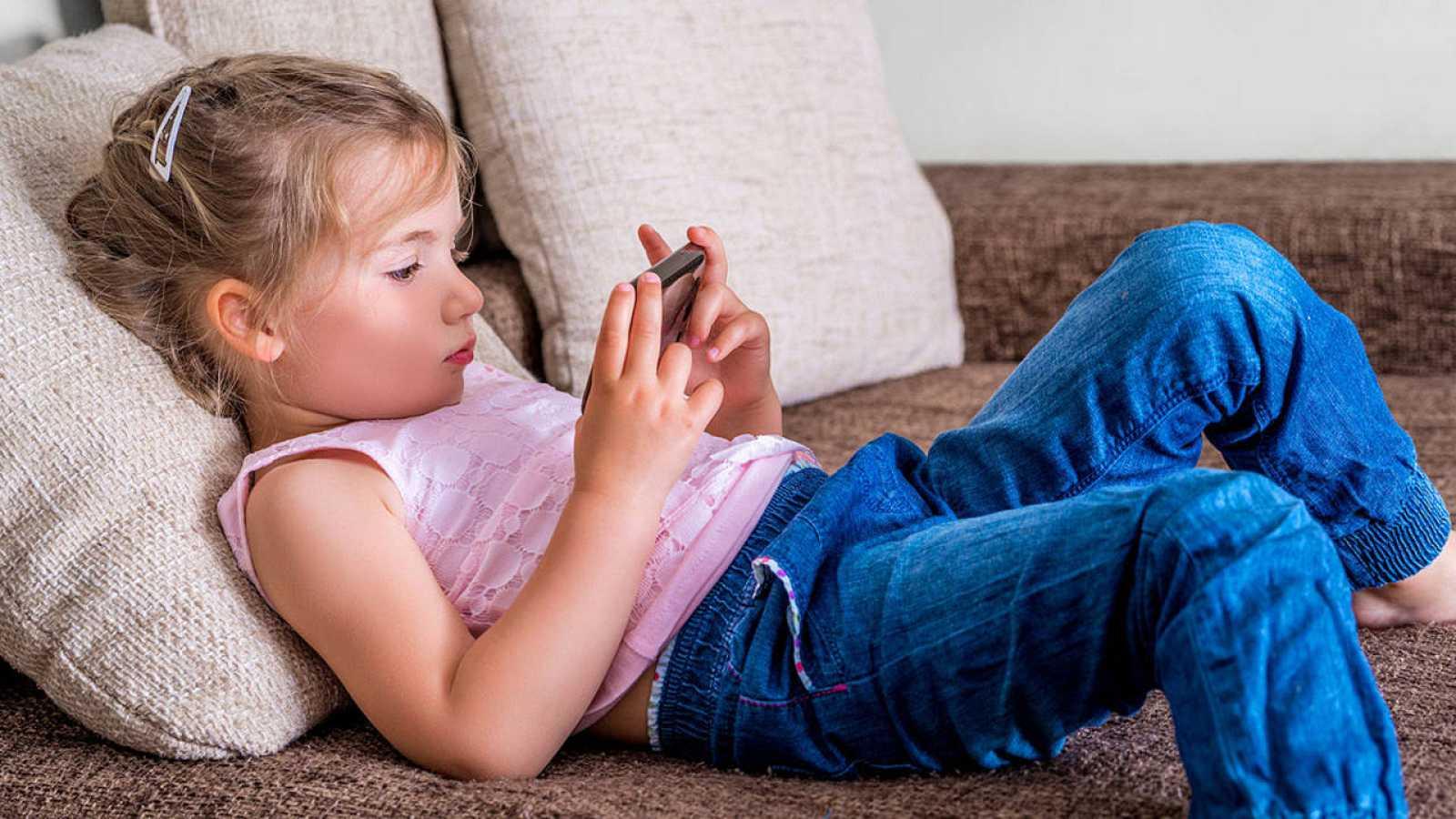 Una niña tumbada en un sofá usa un teléfono móvil