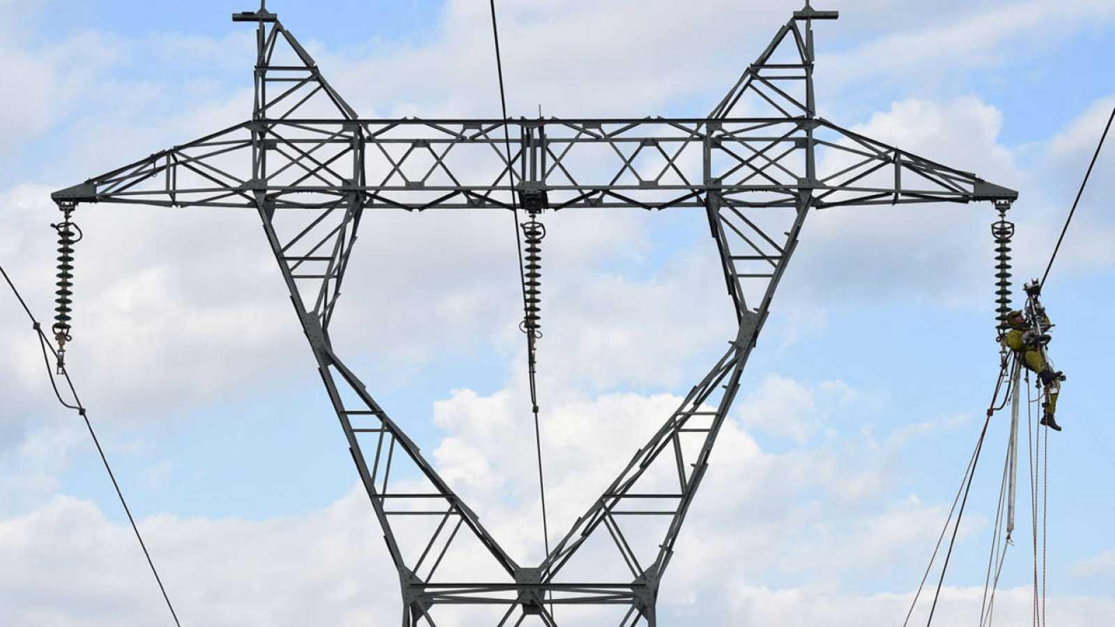 Un electricista trabaja en una torre de alta tensión