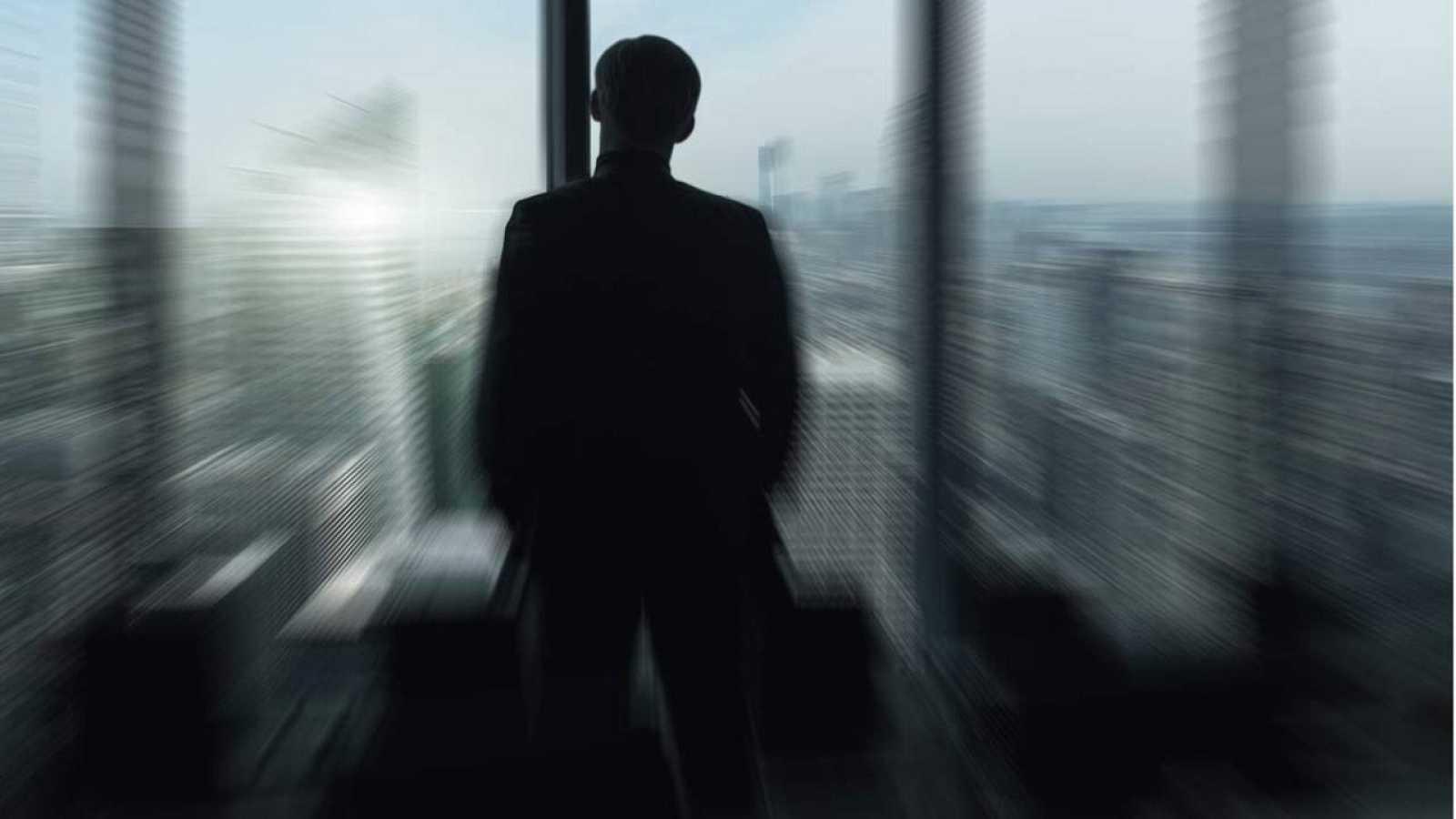Imagen simbólica de un líder mirando a contraluz un horizonte urbano a través de una ventana.