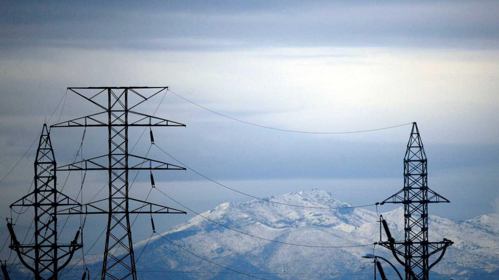 Torres de alta tensión se recortan contra las montañas nevadas que rodean la ciudad de Valencia