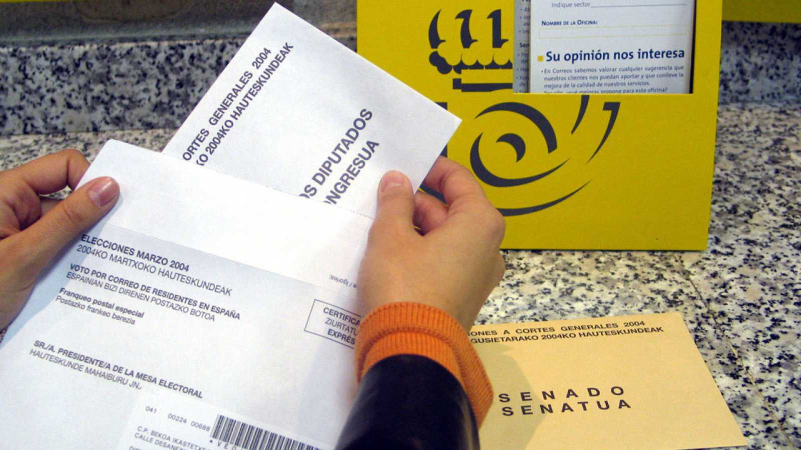 Imagen de archivo en el que una ciudadana deposita su voto por correo en una oficina postal.