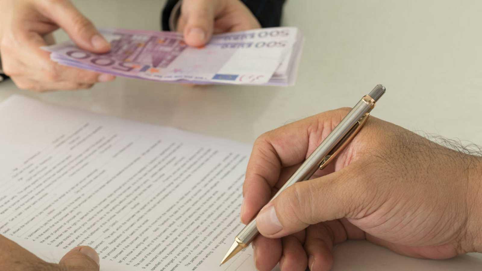 Un cliente firma un contrato de préstamo en una entidad