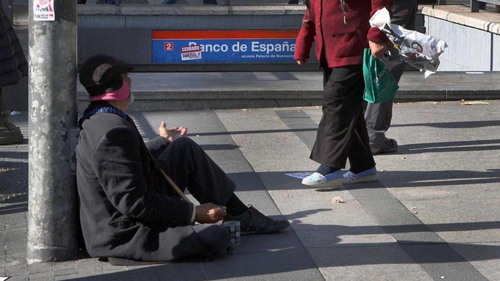 Un anciano mendiga junto a una salida del Metro en el centro de Madrid