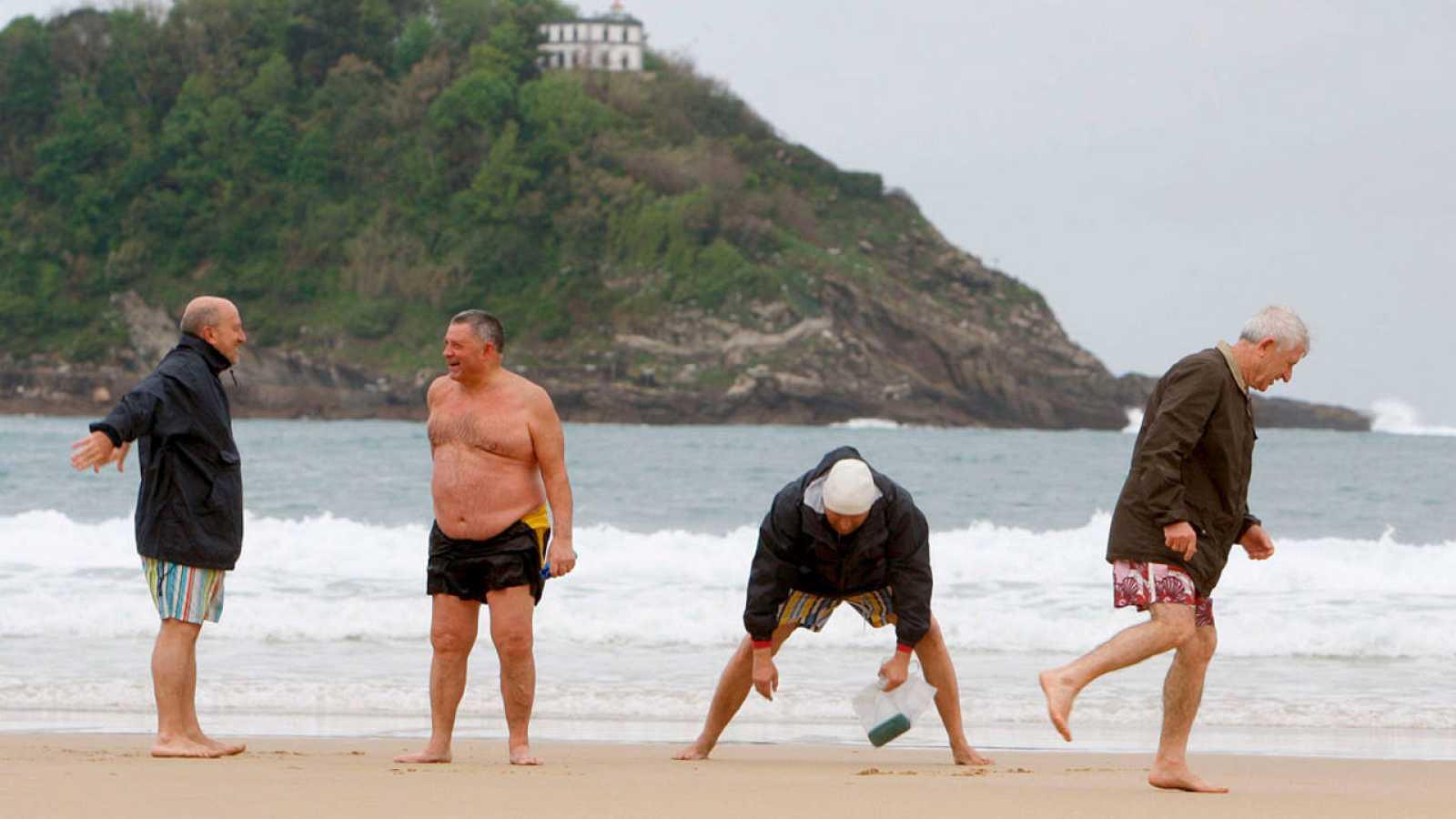 Unos jubilados disfrutan de la playa de la Concha en San Sebastián