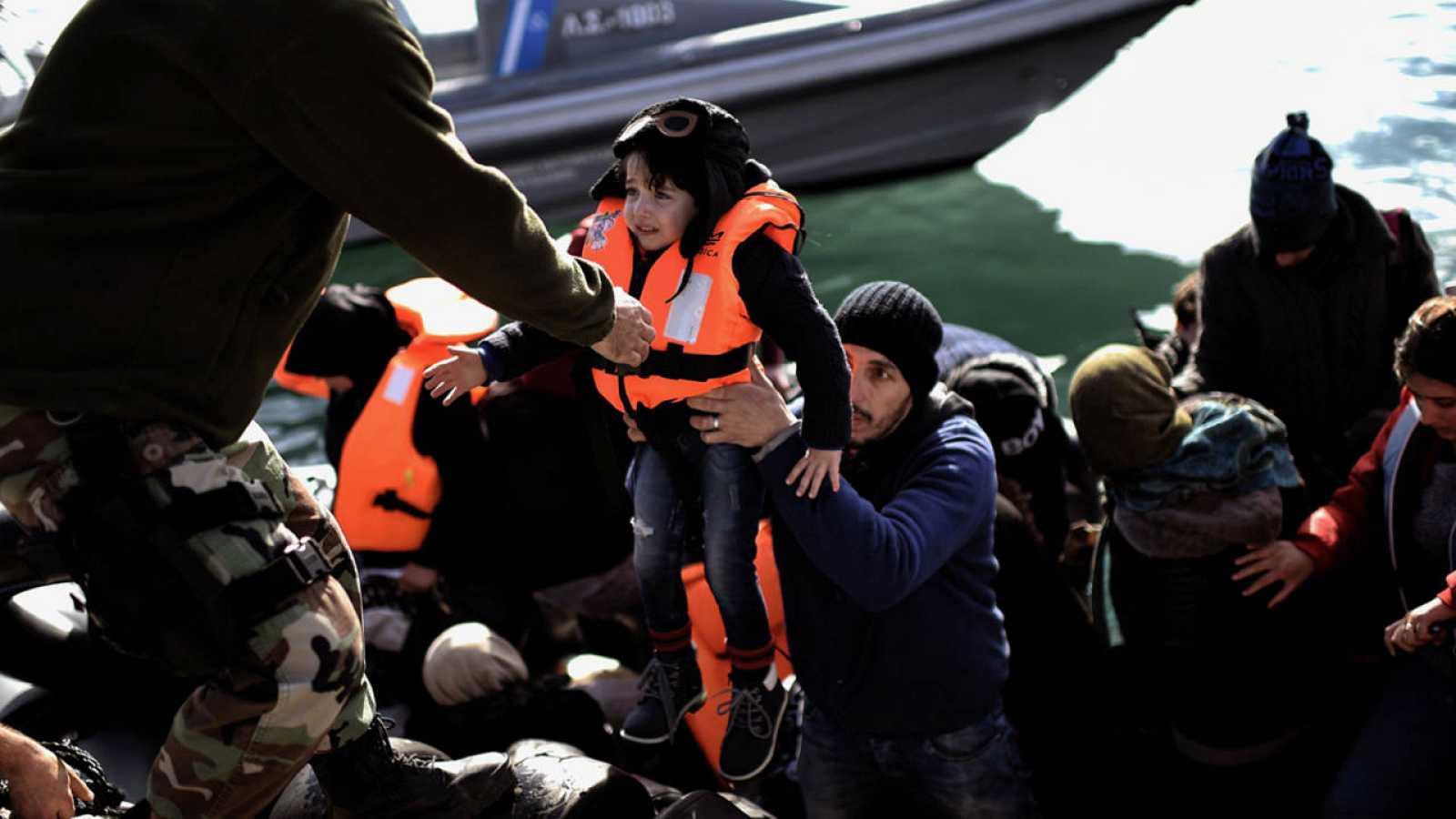 Un guardia costero griego ayuda a un menor refugiado a desembarcar en el puerto de Mytilene, en la isla griega de Lesbos
