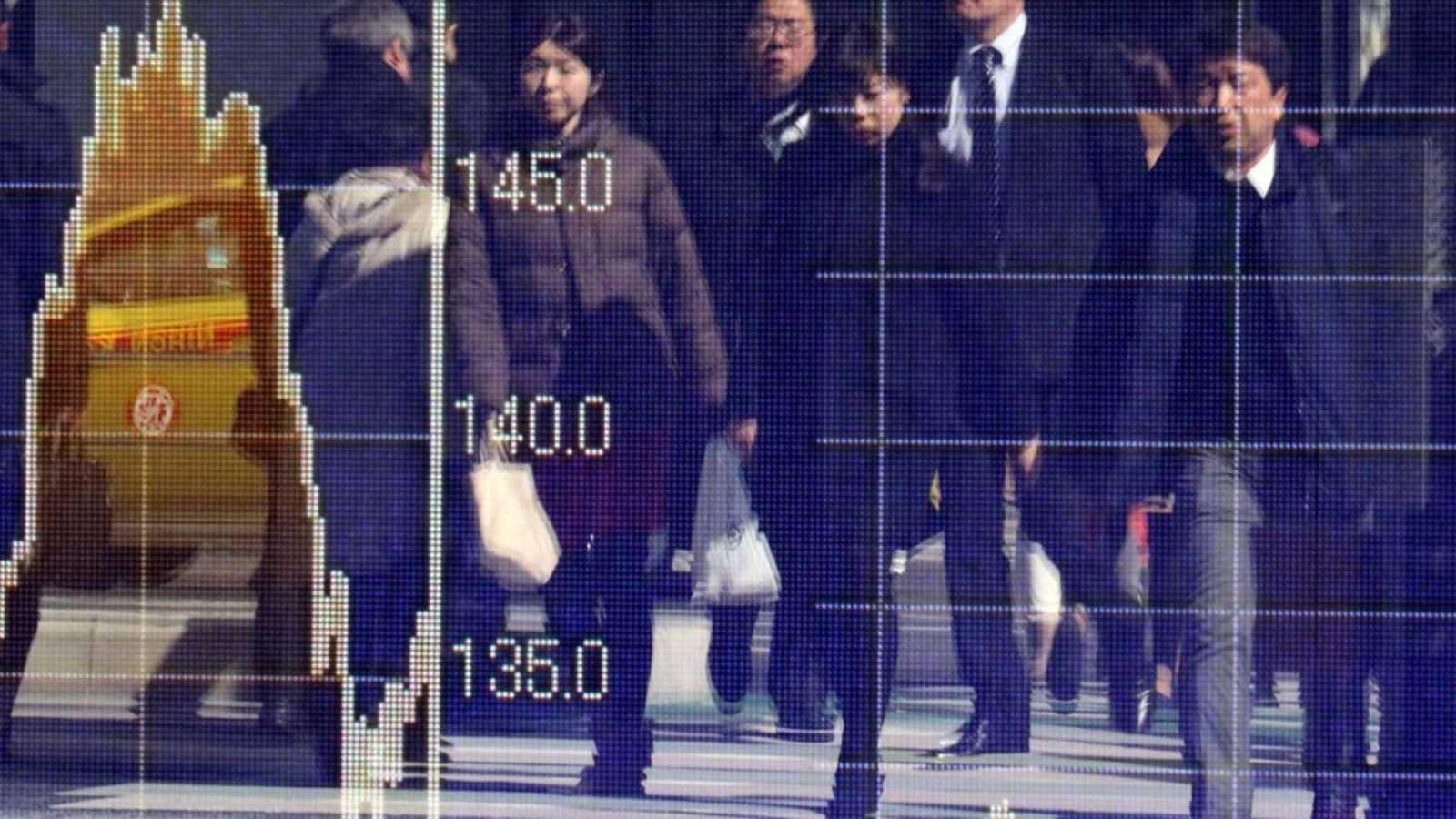 Peatones, reflejados en una pantalla electrónica con los datos de mercados financieros en una calle de Tokio