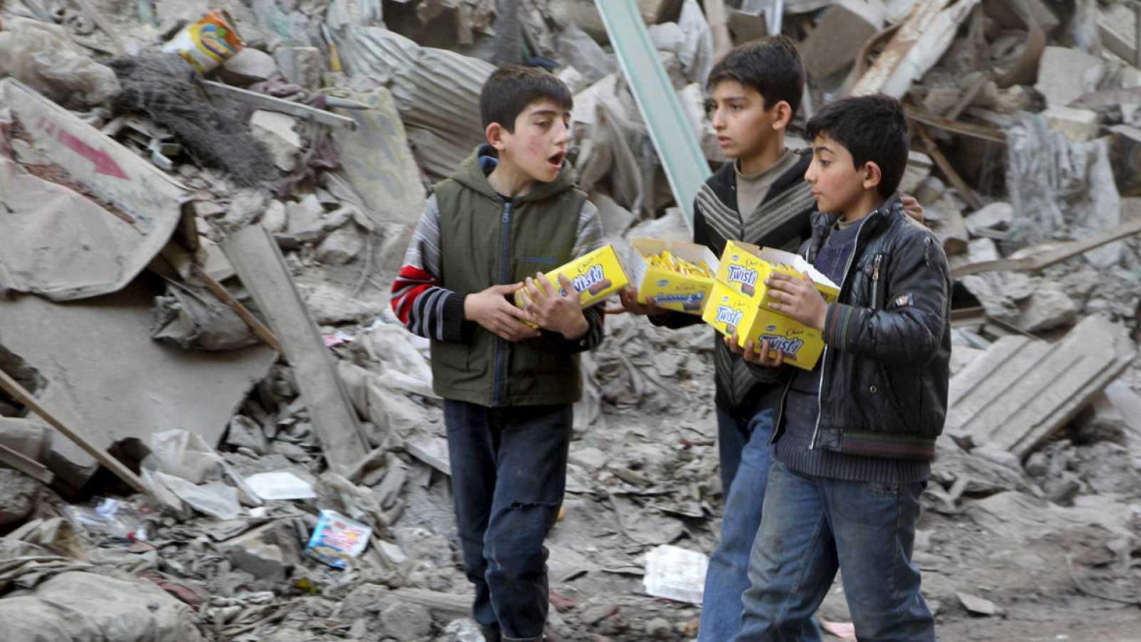Niños sirios llevan cajas de galletas junto a las ruinas de un edificio en Alepo